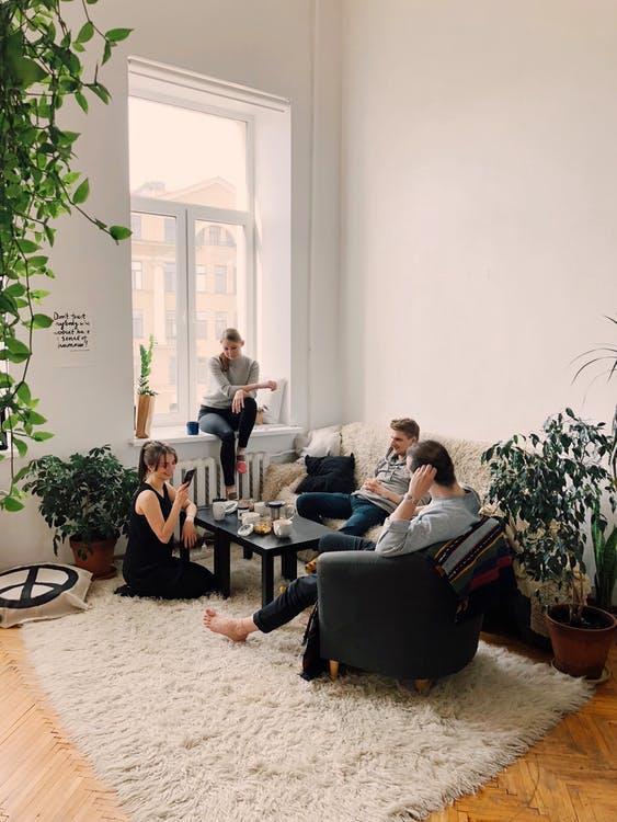 4 junge Leute sitzen bei Sofa und Teppich